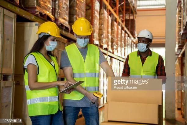 warehouse worker wearing protective mask with with barcode scanner in the shelf. - westen stock-fotos und bilder