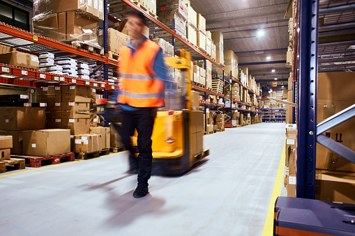 Warehouse, worker with a forklift in motion blur. 1143020296
