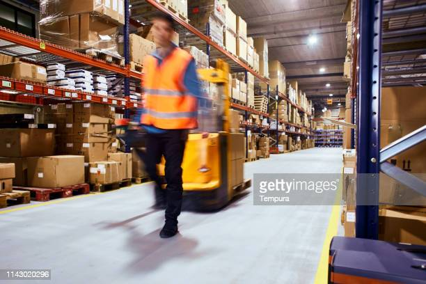warehouse, worker with a forklift in motion blur. - mercanzia foto e immagini stock