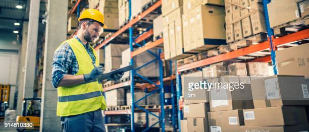 Warehouse worker with clipboard checking packages