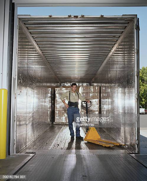 Warehouse worker with dolly inside delivery truck