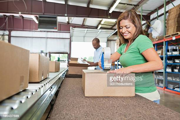 Warehouse workers assembling packages for distribution in assembly line