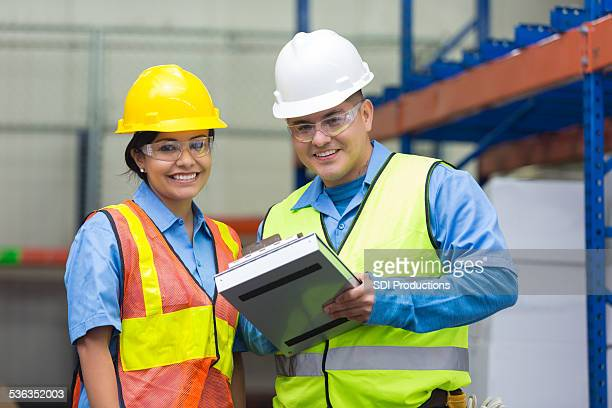 Warehouse workers checking inventory list on clipboard