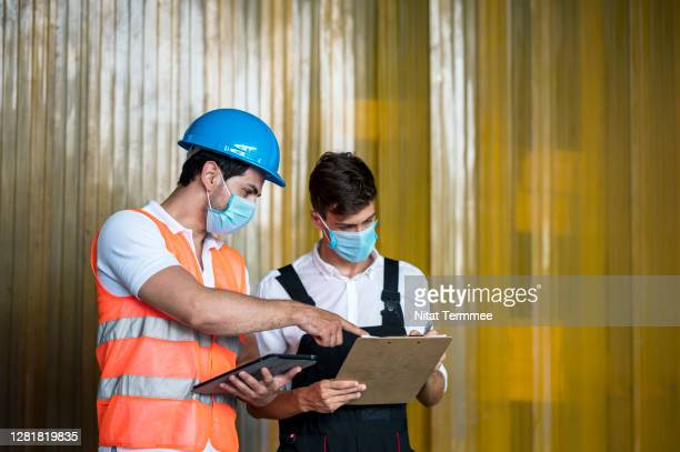 warehouse workers discussion on taking inventory report together at frozen food warehouse. - hygiene stock pictures, royalty-free photos & images