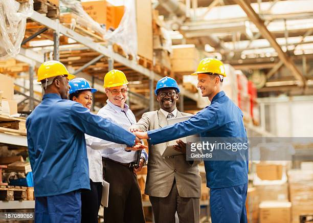 Warehouse workers joining hands