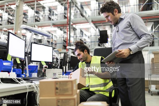 Warehouse workers preparing parcel for delivery