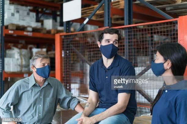 lagerarbeiter im gespräch - izusek stock-fotos und bilder