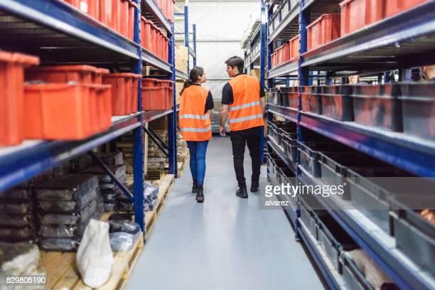 Warehouse workers walking through large shelves