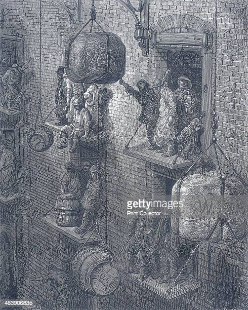 'Warehousing in the City' 1872 showing warehouse workers using rope pulleys to hoist barrels and packages at a warehouse in the City of London Taken...