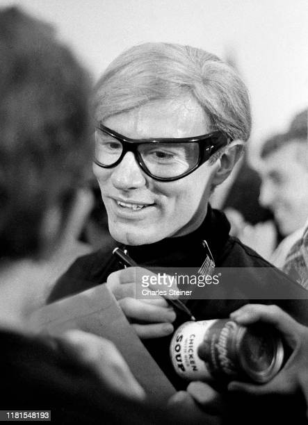 Warhol autographs an actual Campbell's Chicken Soup can at the opening party of his first museum exhibition at the Institute of Contemporary Art on...