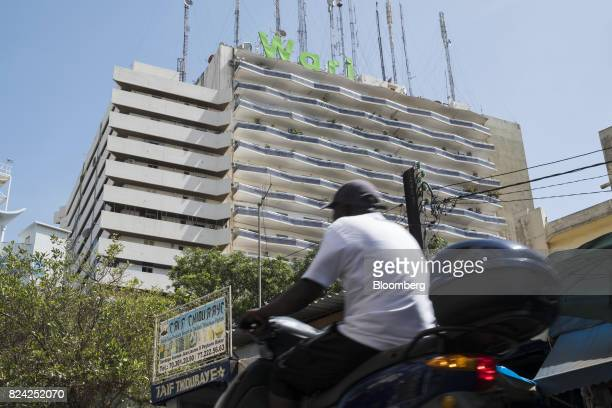A Wari logo stands on top of a building as a moped rider passes by in the Plateau district of Dakar Senegal on Friday July 28 2017 Senegalesevoters...