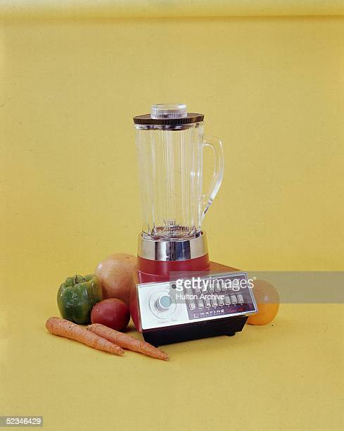 A Waring Futura 1000 blender sits amid fruits and vegetables against a yellow background 1970s