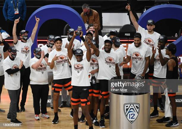 Warith Alatishe of the Oregon State Beavers holds up the most outstanding player award as the team celebrates their 70-68 victory over the Colorado...