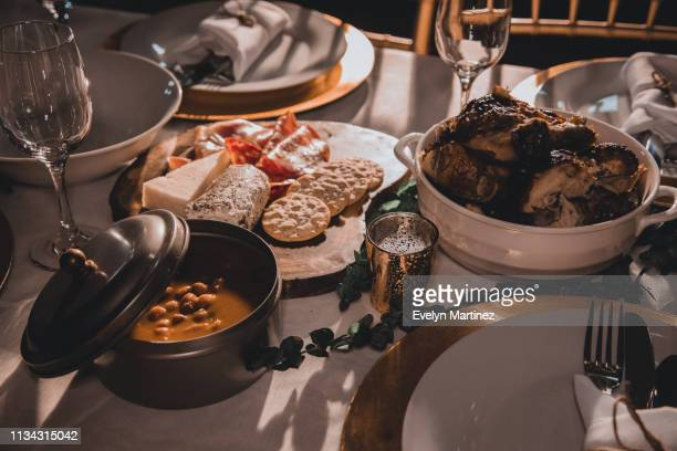 warm colored photo of dinner table set up. metal container of beans (habichuelas), appetizers, and chicken in the frame. out of focus: napkin wrapped flatware on empty dinner plates. glasses and partial views of chairs at the table. - evelyn martinez stock pictures, royalty-free photos & images