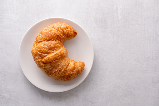 Warm crispy flaky croissant roll on white plate and distressed table 1161699327