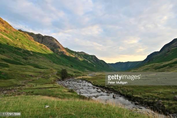 warm dawn light illuminates a mountain ridge in the english lake district - prado fotografías e imágenes de stock