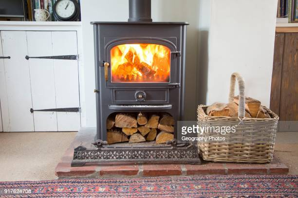 Warm fire flames logs burning in ClearView domestic multifuel stove burner inside home, UK.