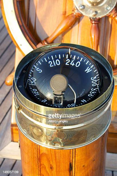 A warm glow highlights the ship's wheel and compass on board a classic sailing yacht as sunset approaches.