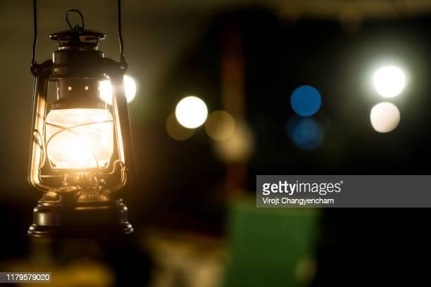 warm light of lantern, outdoor and camping life concept - ランタン ストックフォトと画像