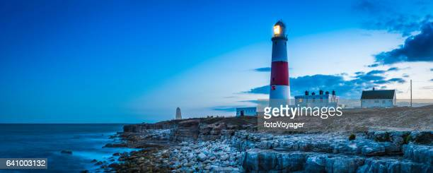 Warm light of lighthouse glowing over rocky ocean shore panorama