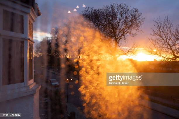 Warm, orange light from a late, flaring sunset shines through condensation in a window that overlooks a residential street and tall trees in south...