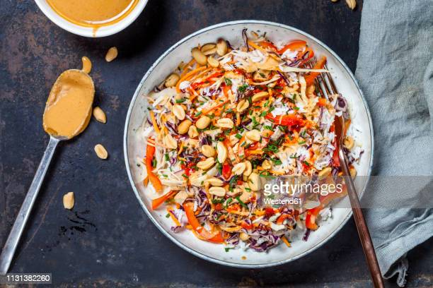 Warm rice salad with grated vegetables, peanut sauce and peanuts