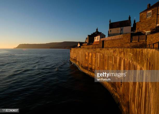 Warm sunlight is reflected from buildings and the sea wall at Robin Hood's Bay on February 26 2019 in Robin Hood's Bay England Warm weather continues...