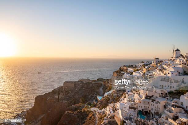 warm sunset over oia village, santorini greek islands - oia santorini foto e immagini stock