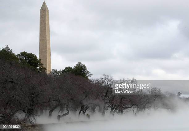 Warm weather causes fog to rise from the ice on the Tidal Basin near the Washington Monument on January 12 2018 in Washington DC