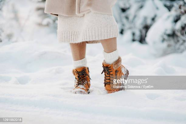 warm winter boots in the snow. a girl in a beige faux fur coat walks through a snowy forest. fashion - snow boot stock pictures, royalty-free photos & images