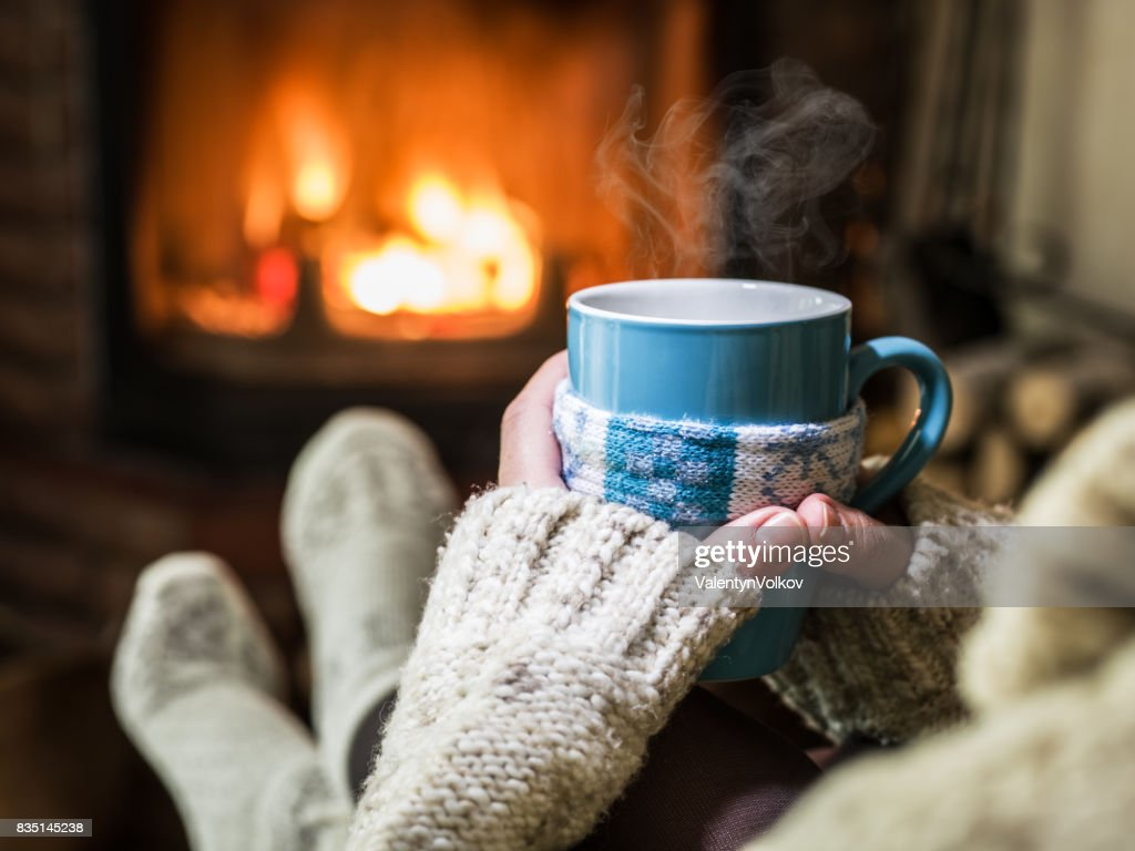 Warming and relaxing near fireplace with a cup of hot drink. : Stock Photo