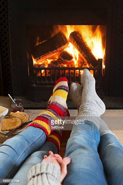 warming feet by the fire - warming up stock pictures, royalty-free photos & images