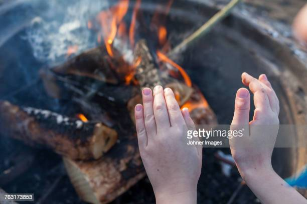 Warming hands at fire
