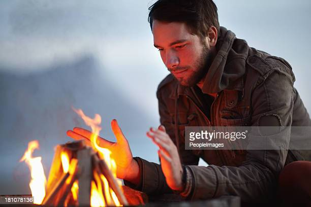 warming himself at the flames - camp fire stock photos and pictures