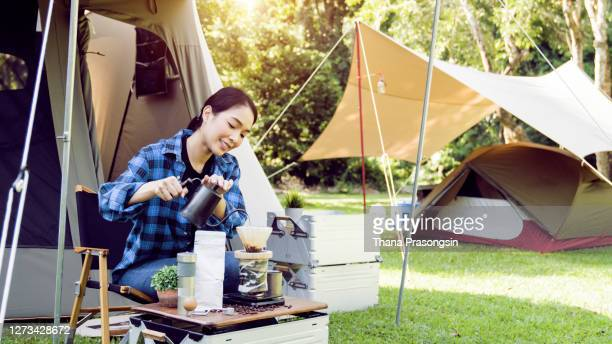 warming up next to the campfire - キャンプ 1人 ストックフォトと画像