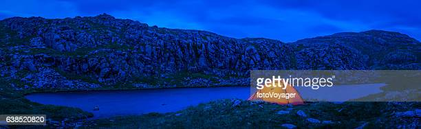 Warmly illuminated dome tent camping beside blue mountain lake panorama