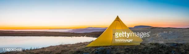 Warmly illuminated mountain tent overlooking misty lake ridges panorama sunrise