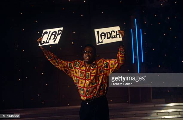 BBC warmup man Miles Crawford holds up two boards prompting the audience watching the National Lottery Show to Clap or Laugh in BBC Television Centre...