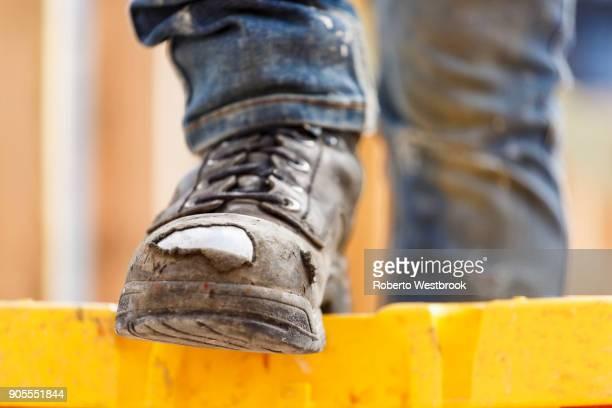 warn boot of caucasian woman at construction site - stiefel stock-fotos und bilder