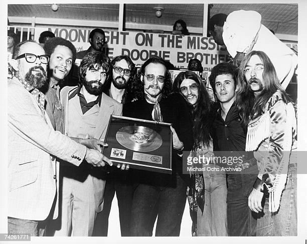 Warner Brothers chairman of the board Mo Ostin, gives a gold record to Tiran Porter, Mike McDonald, Keith Knudson, John Hartman, Patrick Simmons,...