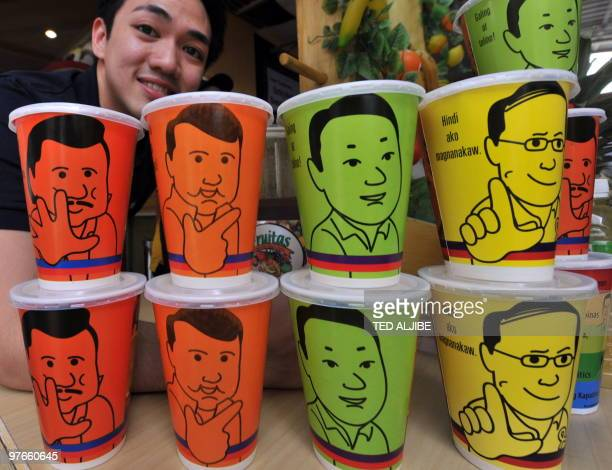 Warner Lee spokesman for the furitjuice chain poses next to cups emblazoned with a portraits of Philippine presidential candidates former president...