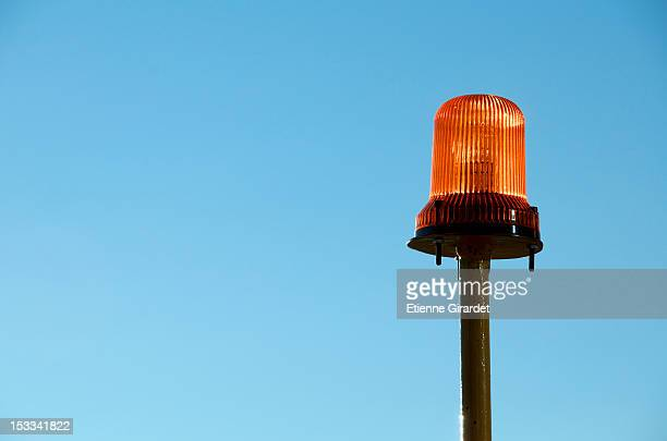 Warning light with blue background of sky