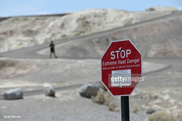 Warning sign alerts visitors of heat dangers at Zabriskie Point on July 11, 2021 in Death Valley National Park, California. An excessive heat warning...