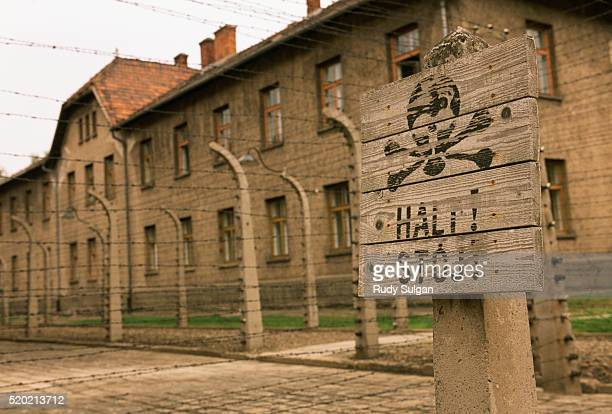 warning sign and fence at auschwitz concentration camp - auschwitz concentration camp stock pictures, royalty-free photos & images