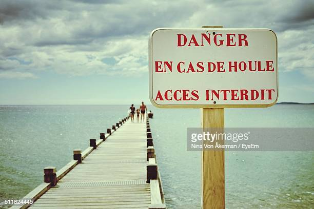 Warning sign and seascape with pontoon bridge