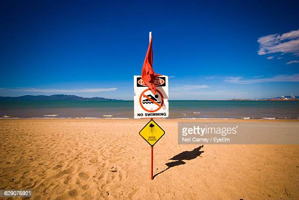 Warning Sign At Beach Against Sky