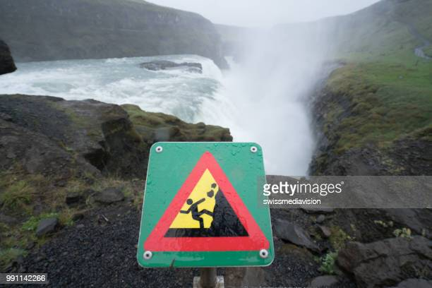 Warning sign at Gulfoss waterfalls in Iceland, overcast day, water mist