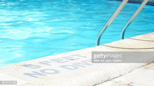 warning sign at poolside during sunny day - poolside stock pictures, royalty-free photos & images