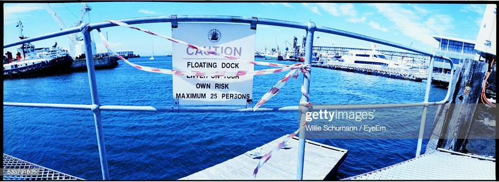 Warning Sign Attached To Pier Barrier And Sea With Ships In Background : Foto stock