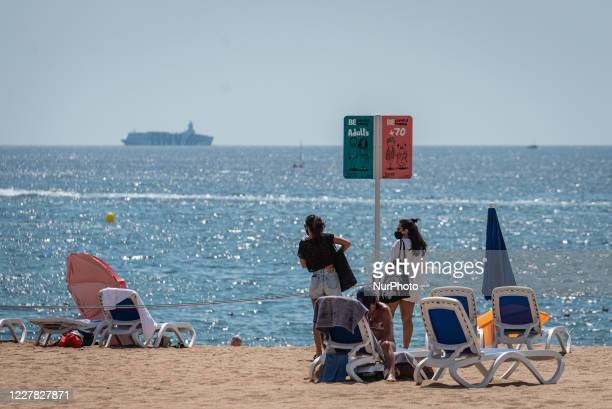 Warning sign in Lloret de Mar beach to separate old people and families or young people area Summer season in Lloret de Mar is being bad after the...